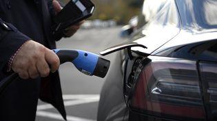 Un homme recharge son véhicule électrique. Photo d'illustration. (DANIEL LEAL-OLIVAS / AFP)