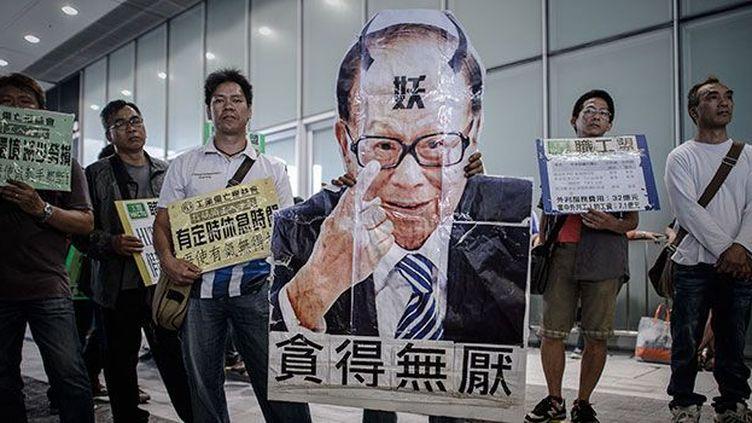Les dockers brandissent des pancartes à l'effigie de Li Ka-shing, homme d'affaire milliardaire et président du groupe Watson, numéro un mondial de la gestion de ports dans le monde. (AFP PHOTO / Philippe Lopez)