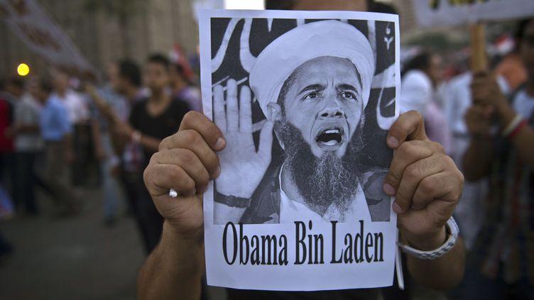 Un manifestant place Tahrir, au Caire(Egypte), brandit, le 7 juillet 2013, une affichette caricaturant Barack Obama enOussama Ben Laden. (KHALED DESOUKI / AFP)