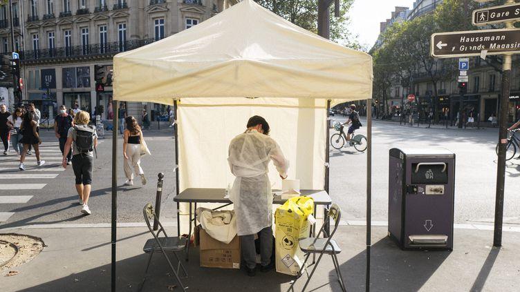 Un homme prépare des tests antigéniques sous une tente, à Paris, le 6 septembre 2021. (NICOLAS PORTNOI / HANS LUCAS / AFP)