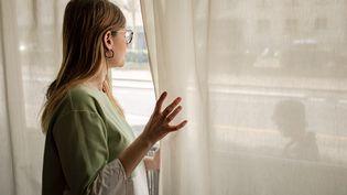 Illustration d'une jeune femme chez elle pendant le confinement. (JULIEN HELAINE / HANS LUCAS / AFP)