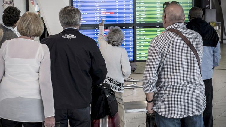 Des passagers vérifient leur vol à l'aéroport de Lyon-Saint-Exupery, le 15 septembre 2014. (JEAN-PHILIPPE KSIAZEK / AFP)