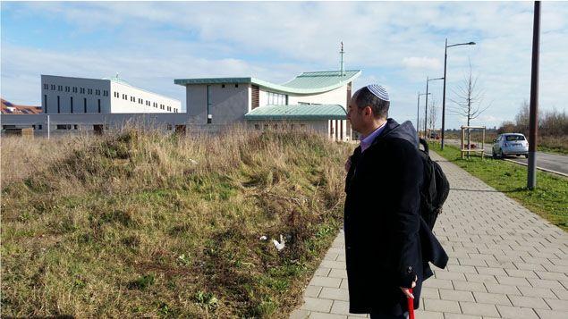 (Le rabbin Guy Bénarousse devant le terrain en friche qui accueillera la synagogue juste à côté de la mosquée © RADIOFRANCE / Benjamin Illy)
