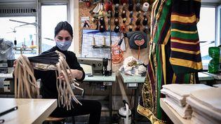Une couturière fabriquant des masques de protection dansl'atelierde l'opéra de Marseille, 20 avril 2020 (ANNE-CHRISTINE POUJOULAT / AFP)