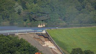 Un hélicoptère de la Royal Air Force largue des sacs de sable pour endiguer l'effondrement du barrage de Toddbrook, dans le nord de l'Angleterre, le 2 août 2019. (ROLAND HARRISON / AFP)