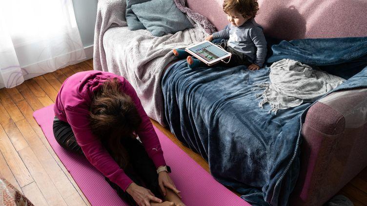 Une femme fait des exercices de pilates et stretching sur un tapis en suivant un cours sur internet. (RICCARDO MILANI / HANS LUCAS)