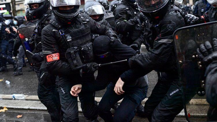 """Un manifestant est tenu par deux policiers lors de la manifestation contre la proposition de loi """"Sécurité globale"""", à Paris, le 12 décembre 2020. (MARTIN BUREAU / AFP)"""