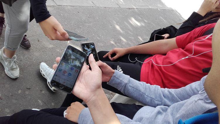 Des enfants comparent leurs téléphones portables dans une cour de récréation. (LAURENT WATRIN / FRANCE-BLEU SUD LORRAINE)