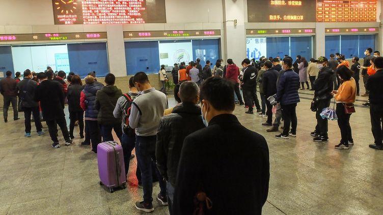 Des voyageurs patientent à la gare de Yichang, dans le Hubei, le 25 mars 2020. (AFP)