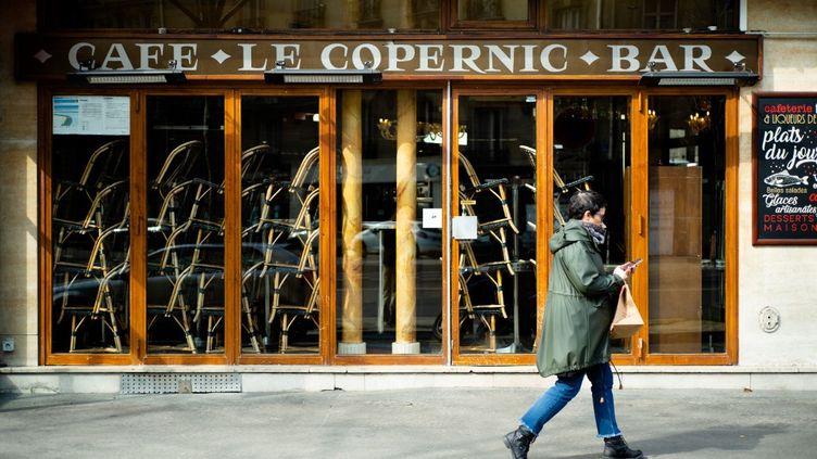 Une femme passe devant un café fermé, à Paris, le 20 mars 2020. (EDOUARD RICHARD / HANS LUCAS / AFP)