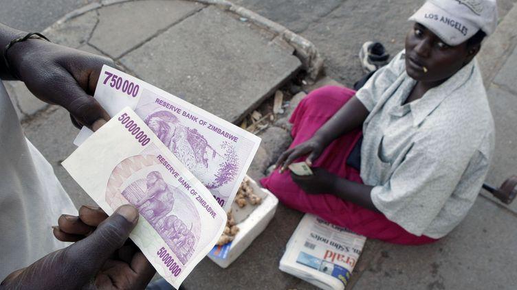 Un Zimbabwéen tient un billet de 50 millions de dollars dans une rue de la capitale Harare. En 2008, l'inflation avait atteint letaux astronomique de 100.000 %. (MIKE HUTCHINGS / X00388)