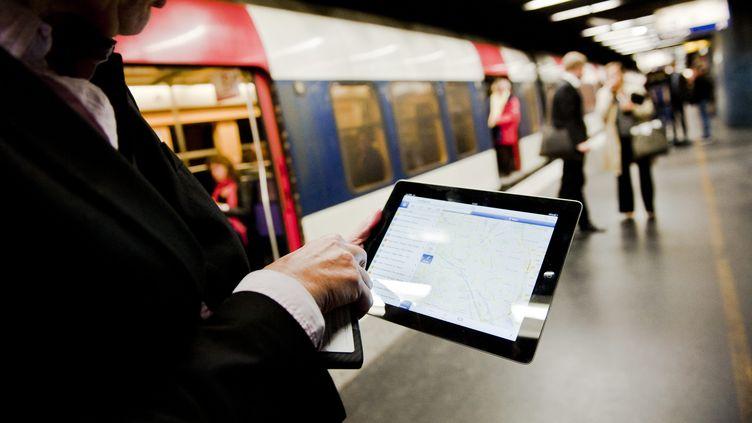 Un homme consulte internet sur sa tablette tactile, sur un quai de la ligne du RER A, à Paris, le 4 octobre 2012. ( MAXPPP)