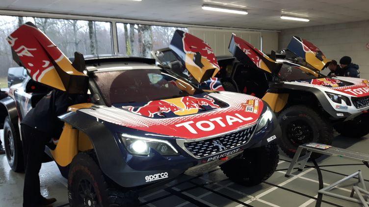 Sur un circuit privé de PSA, à la Ferté-Vidame, en Normandie, les deux voitures 3008 DKR Maxi numéro 306 de Sébastien Loeb et 303 de l'Espagnol Carlos Sainz sont examinées par les ingénieurs et les mécaniciens. (GUILLAUME BATTIN / RADIOFRANCE)