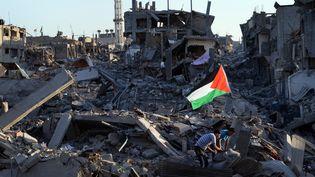 Des Palestiniens dans les décombres à Gaza, le 7 août 2014. (ROBERTO SCHMIDT / AFP)