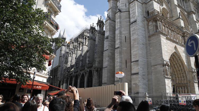 Des touristes viennent photographier la cathédrale Notre-Dame de Paris après l'incendie, le 15 juin 2019. (ZAKARIA ABDELKAFI / AFP)