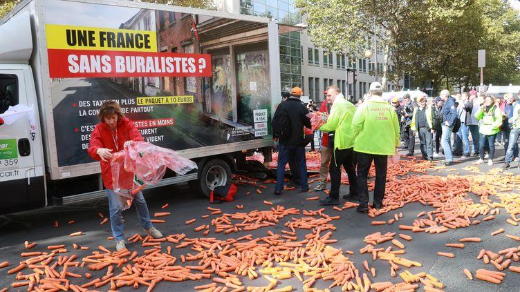 Manifestation de buralistes dans Paris. Ils déversent des carottes devant le ministère de la Santé, le 4 octobre 2017 (JACQUES DEMARTHON / AFP)