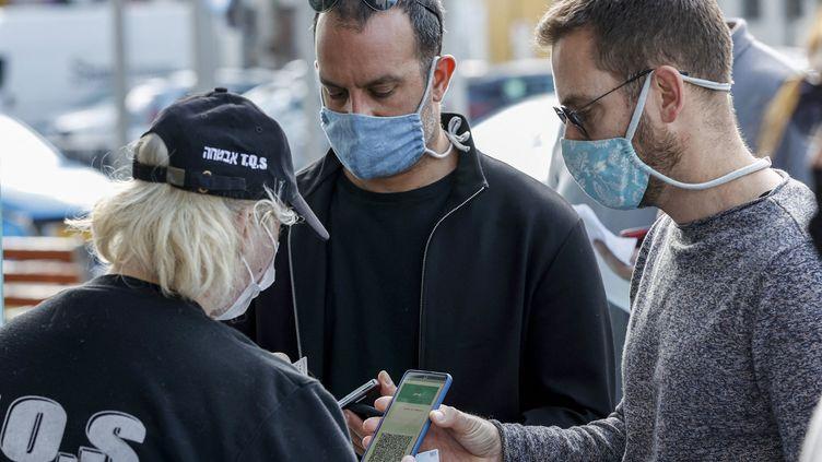 """Des clients montrent leur """"passeport vert"""" à l'entrée d'un stade à Tel Aviv (Israël), le 5 mars 2021. (JACK GUEZ / AFP)"""