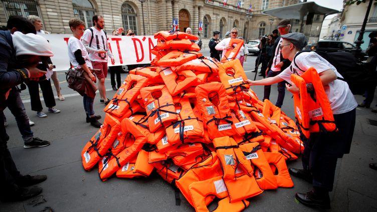 Empilement de gilets rouges devant le Sénat à Paris, symbole des migrants morts en Méditerranée.Une action militante, le 19 juin 2018, à l'occasion du débat sur l'immigration et le droit d'asile. (CHARLES PLATIAU / X00217)
