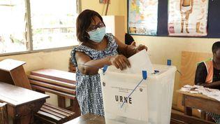 Une femme vote dans un bureau d'Abidjan le 6 mars 2021, lors des élections législatives en Côte d'Ivoire. (CYRILLE BAH / ANADOLU AGENCY)