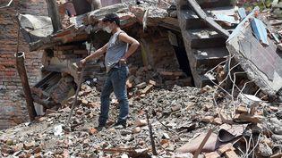Un habitant népalais nétoie les débris de sa maison à Katmandou le 27 avril 2015. (PRAKASH SINGH / AFP)