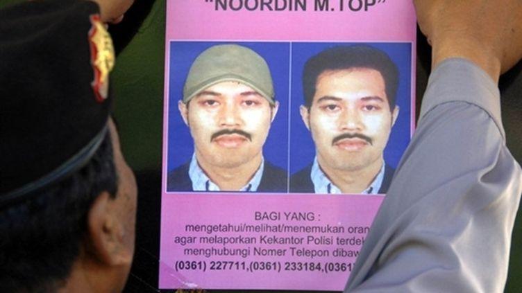 Un policier affiche un avis de recherche de Noordin Top, l'homme le plus recherché d'Indonésie (juillet 2009) (© AFP / Sonny Tumbelaka)
