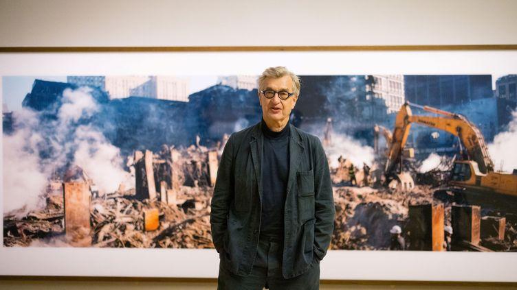 Wim Wenders devant l'une de ses photos du site de Ground Zero, le 10 septembre 2021 à Londres (TOLGA AKMEN / AFP)