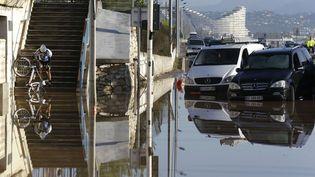 L'étendue des inondations à Biot n'a pas empêché ce courageux cycliste de tenter de faire sa promenade dominicale. (LIONEL CIRONNEAU / AP / SIPA)