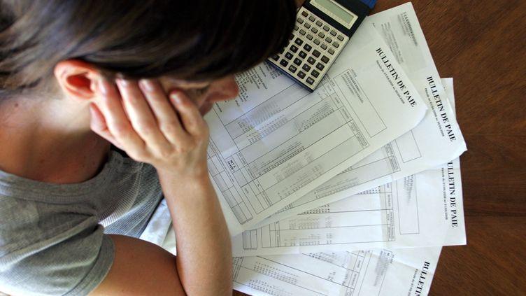 Une salariée étudie ses feuilles de paie. (MAXPPP)