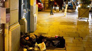 Un homme dort dans une rue du quartier du Marais, à Paris, le 14 décembre 2019. (EDOUARD RICHARD / HANS LUCAS / AFP)