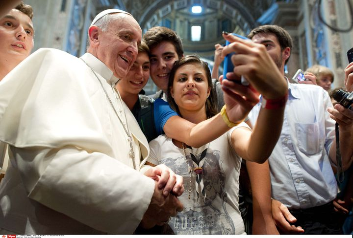 """Le pape François pose pour un """"selfie"""" à l'intérieur de la basilique Saint-Pierre (Vatican), le mercredi 28 août 2013. (SIPA / AP)"""