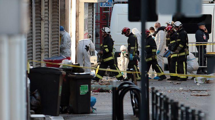 Les experts de la police et les pompiers travaillent à l'extérieur d'un immeuble de Saint-Denis (Seine-Saint-Denis), le 18 novembre 2015, après un assaut mené par les forces de l'ordre. (JOEL SAGET / AFP)