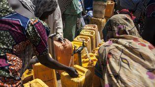 Des femmes récupèrent de l'eau dans le camp de Bama au nord du Nigeria, le 8 décembre 2016. (STEFAN HEUNIS / AFP)