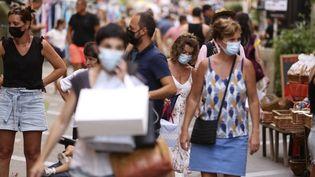 Des passants dans la rue à Ajaccio, en Corse-du-Sud, le 4 août 2021. (PASCAL POCHARD-CASABIANCA / AFP)