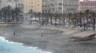 Quelques courageux s'aventurent sur la Promenade des Anglais à Nice (Alpes-Maritimes) alors qu'il neige abondamment, le 26 février 2018. (VALERY HACHE / AFP)