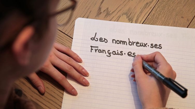 Une personne écrit une phrase en écriture inclusive. (MAXPPP)