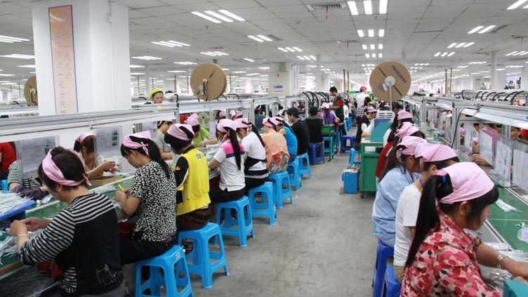 Des ouvriers dans une usine de la société Foxconn Technology, à Fengcheng, en Chine, le 18 mai 2012. (ZOU HAIBIN / IMAGINECHINA / AFP)