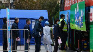 A Pékin, les habitants font la queue pour se faire vacciner contre le Covid-19 dans un bus, le 7 avril 2021. (GREG BAKER / AFP)