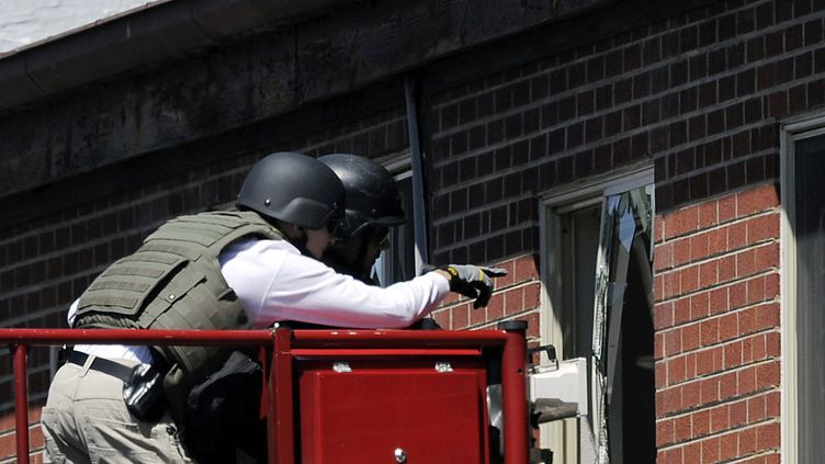 Des officiers de police déminentl'appartement piégé par James Holmes, l'auteur présumé de la fusillade d'Aurora, survenue le 20 juillet 2012 dans la banlieue de Denver, dans le Colorado (Etats-Unis). (CHRIS SCHNEIDER / GETTY IMAGES NORTH AMERICA / AFP)