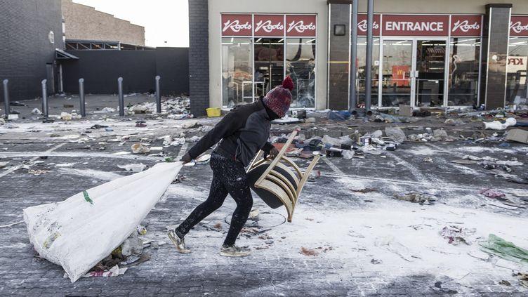 Un homme soupçonné d'être un pillard traîne un sac près d'un magasin vandalisé àVosloorus, dans la banlieue de Johannesbourg, le 14 juillet 2021. (MARCO LONGARI / AFP)