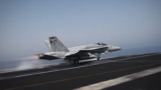 """Un avion de combat américainF/A-18C Hornet décolle du pont du porte-avions """"USS George H.W. Bush"""", le 15 août 2014 dans le Golfe arabo-persique. (MOHAMMED AL-SHAIKH / AFP)"""