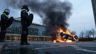 Une voiture brûle àEindhoven, aux Pays-Bas, après une manifestation des opposants au couvre-feu, le 24 janvier 2021. (ROB ENGELAAR / ANP MAG / AFP)