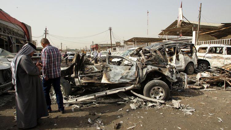 Des Irakiens sur la scène d'un attentat près d'un marché de Bagdad (Irak), le 7 mars 2014. (ALI AL-SAADI / AFP)