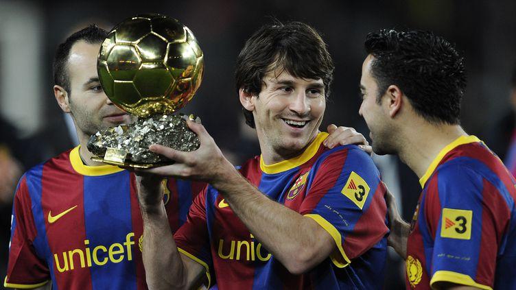 Lionel Messi reçoit le Ballon d'or, devant ses coéquipiers Iniesta (à gauche) et Xavi (à droite), le 12 janvier 2011. (David Ramos / Getty Images)
