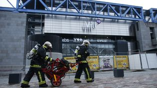 Des sapeurs-pompiers devant la Cité des sciences et de l'industrie à Paris, où un feu s'est déclaré le 20 août 2015. (THOMAS SAMSON / AFP)