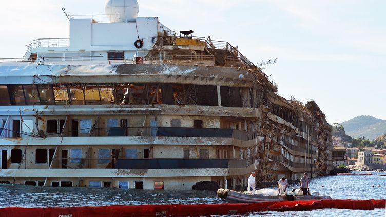 """L'épave du """"Costa Concordia"""", le lendemain de son redressement, le 18 septembre 2013, près de l'île du Giglio (Italie). (VINCENZO PINTO / AFP)"""