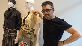 Olivier Châtenet pose à côté d'une silhouette composée d'un polo Lacoste en piqué de coton beige 1940 avec une veste chemise brodée de Yamamoto Kanzai 1980, cravate Hermès  (Corinne Jeammet)