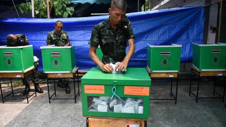 Un soldat thaïlandais dépose son bulletin de vote à Bangkok pour les élections législatives en Thaïlande, le 24 mars 2019. (LILLIAN SUWANRUMPHA / AFP)
