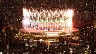 Des feux d'artifice illuminent le ciel au-dessus du stade olympique lors de la cérémonie d'ouverture des Jeux paralympiques de Tokyo 2020, le 24 août 2021. (BEHROUZ MEHRI / AFP)