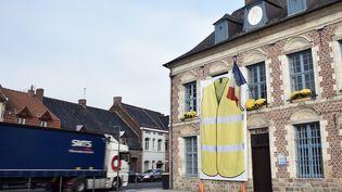 Une affiche avec un gilet jaune sur la façade de la mairie deMorbecque(Nord), le 15 novembre 2018. (FRANCOIS LO PRESTI / AFP)