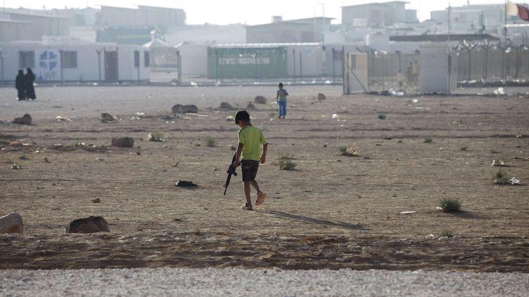 Un petit garçon syrien joue avec une arme en plastique dans le camp de réfugiés de Zaatari, en Jordanie, le 8 août 2013. (MOHAMMAD HANNON / AP / SIPA)